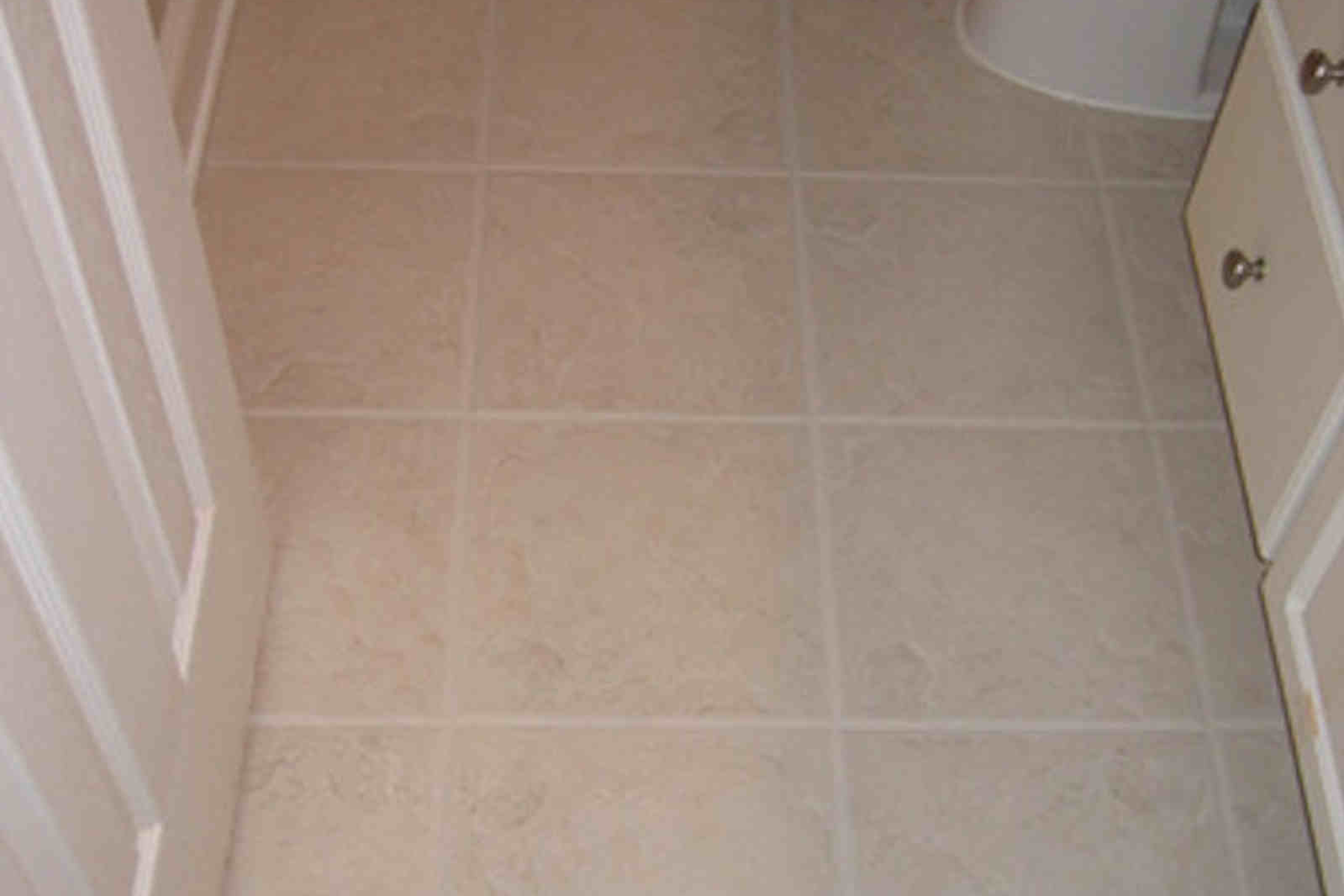 Badly stained bathroom tiles after colour sealing the grout